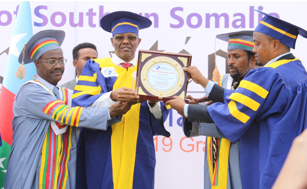 USS Chair, Eng. Abdifatah Samale (right), along with Professors Ali Kusow (2nd right) & M. Eno (left), awarding an institutional accolade to SWSS President, His Excellency Abdiaziz Hassan Mohamed 'Laftagareen' (facing the camera)